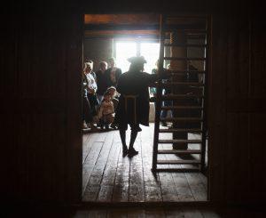 En guide står och berättar om Kronhusets historia för besökare uppe på vinden