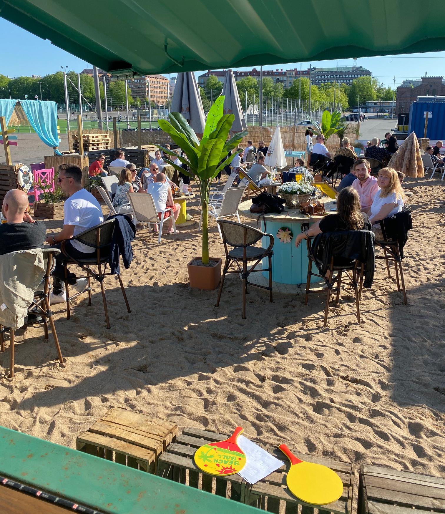 Strandservering vid Heden med matgäster runt runda bord