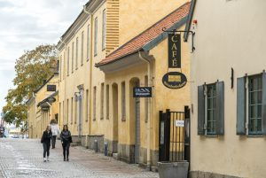 Promenerande människor bredvid de gula stenbyggnaderna Kronhusbodarna.