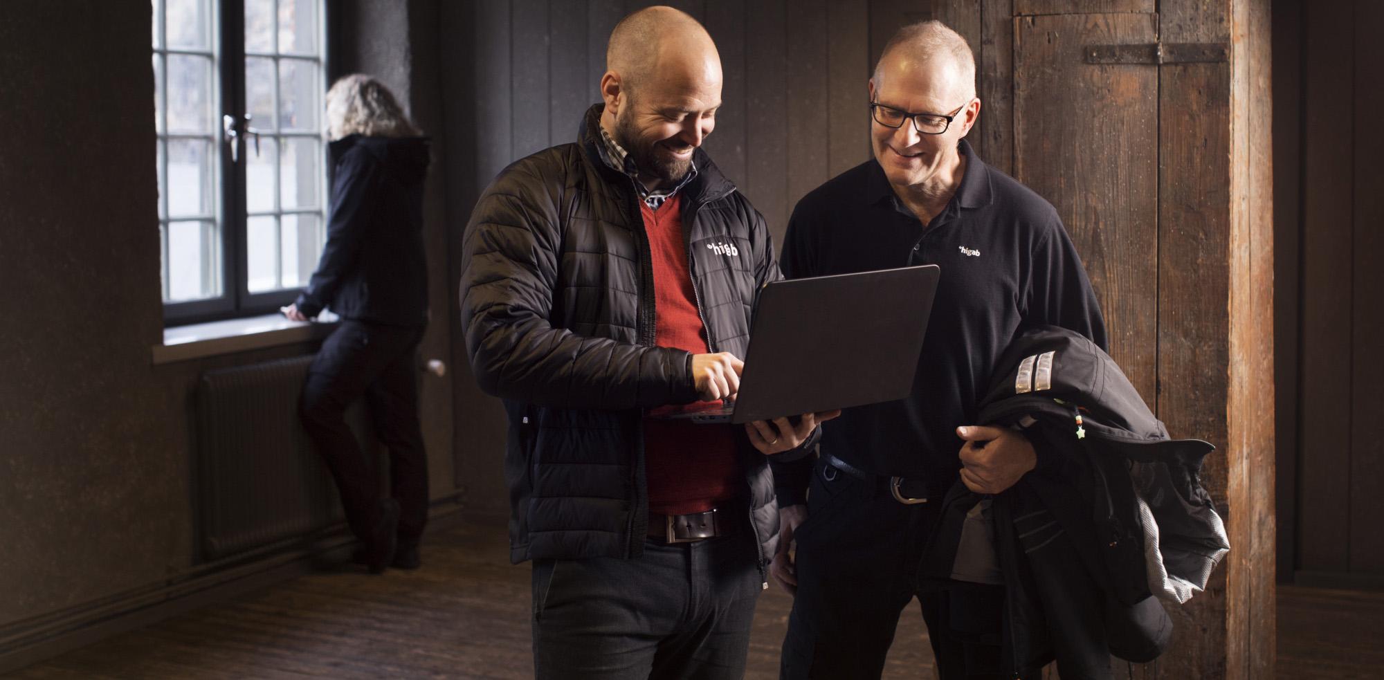 Två Higab-medarbetare står och kollar på skärmen på en bärbar dator.