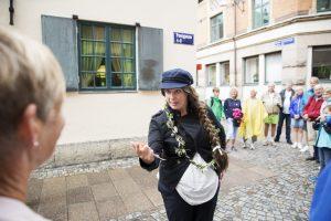 Utklädd guide står på gatan och underhåller en grupp med människor