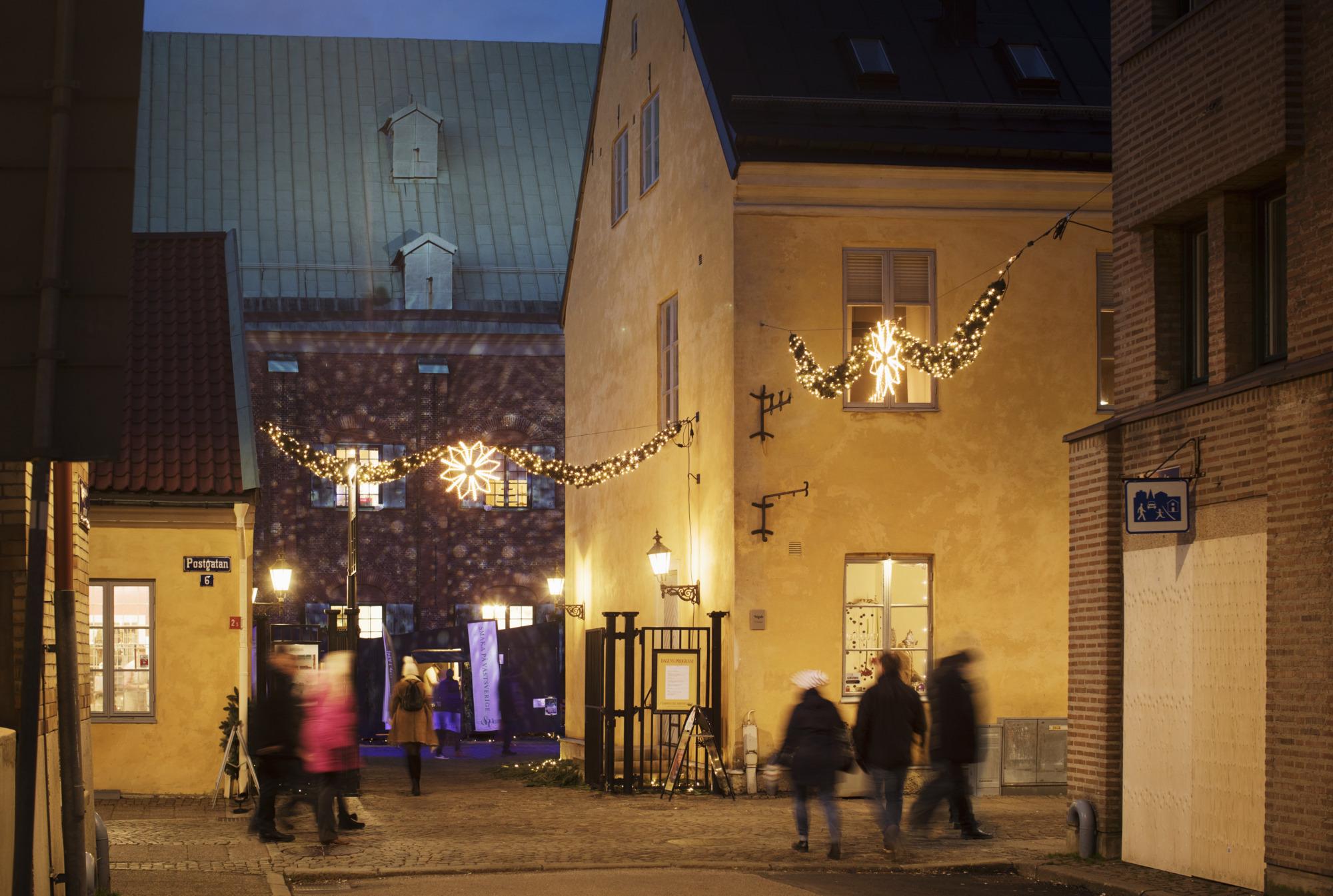Folk i rörelse framför de gula stenbyggnaderna Kronhusbodarna och det röda tegelhuset Kronhuset i Västra Nordstan.