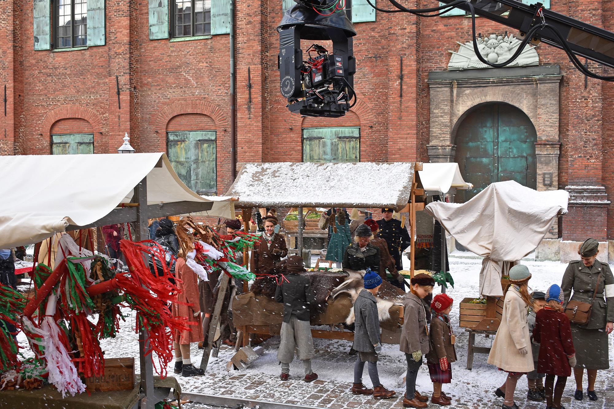 Filminspelning på ett snöfyllt Kronhusgården. Barn står framför julmarknadsstånd.