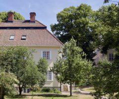 Grönska runt ett gult stenhus med rött tak.