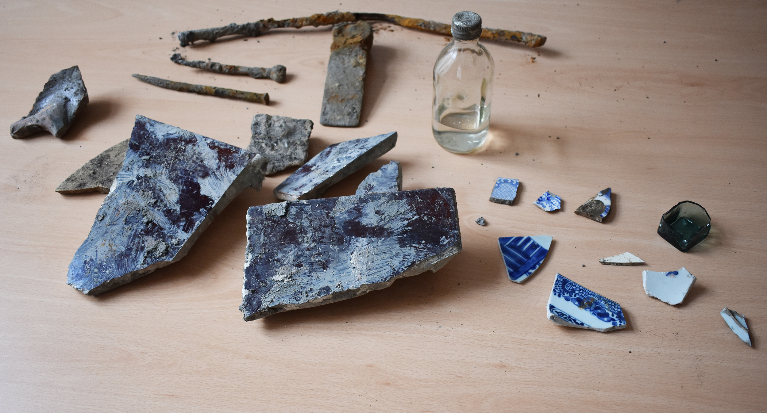 Arkeologiska fynd utspridda på ett bord.
