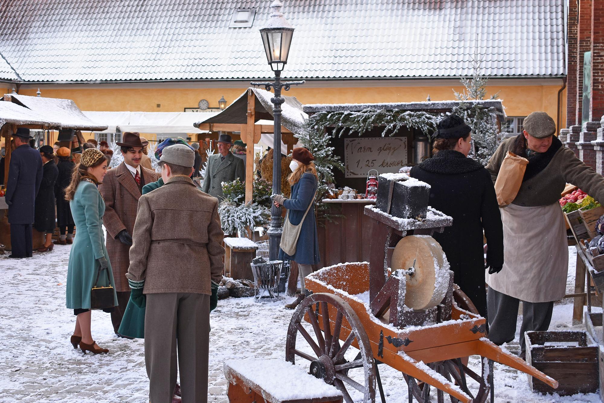 Människor i äldre klädsel står runt julmarknadsstånd på en snöfylld gård.