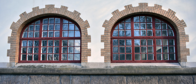 Två stora rundade fönster med smårutsindelning.