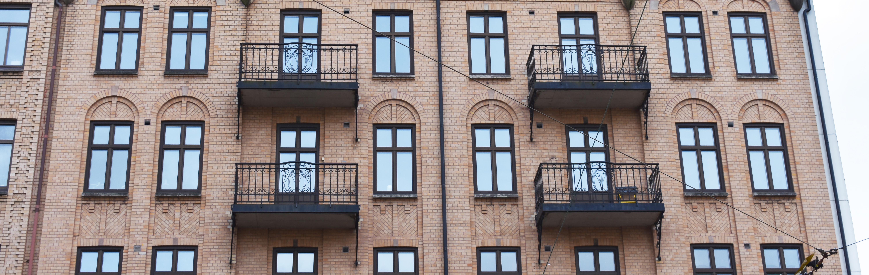 Den gula tegelfasaden med balkonger på Första Långgatan 10.