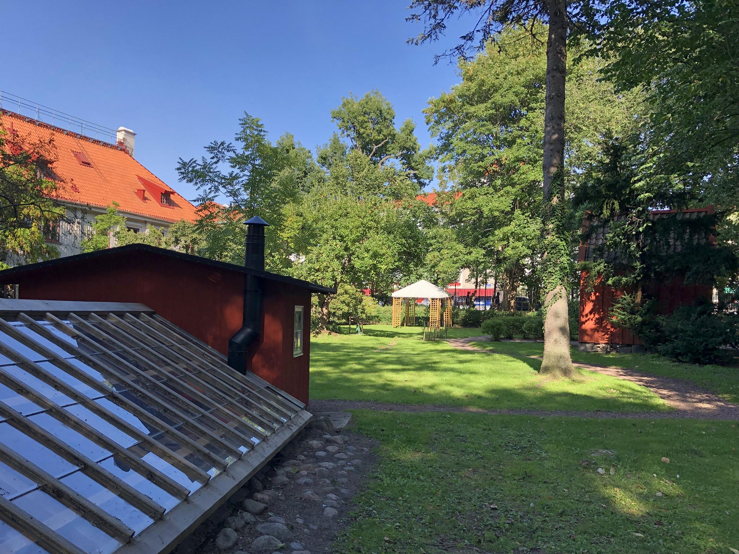 En grönskande trädgård med röda bodar och ett större hus.