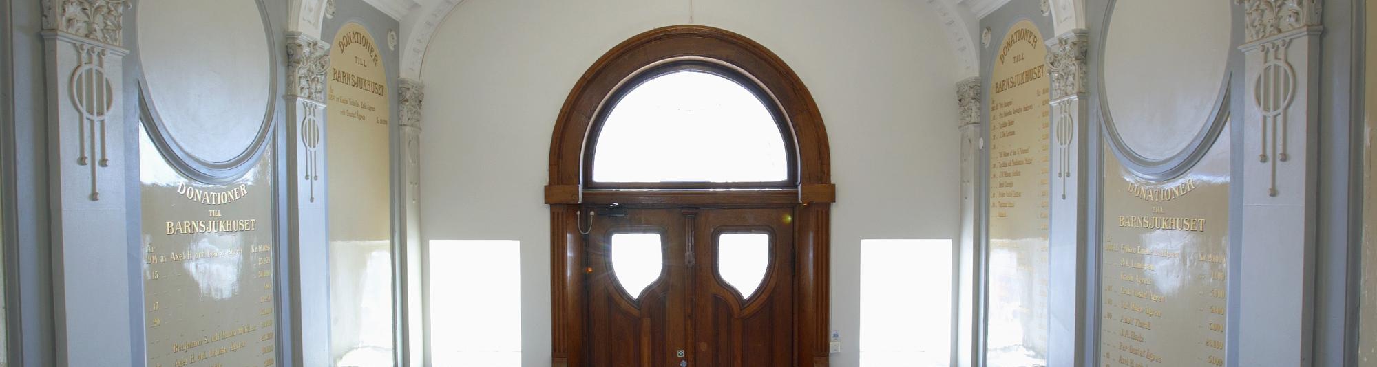 Insidan av entrén till Hälsovetarbacken med rundad träport och dekorerade stenväggar.