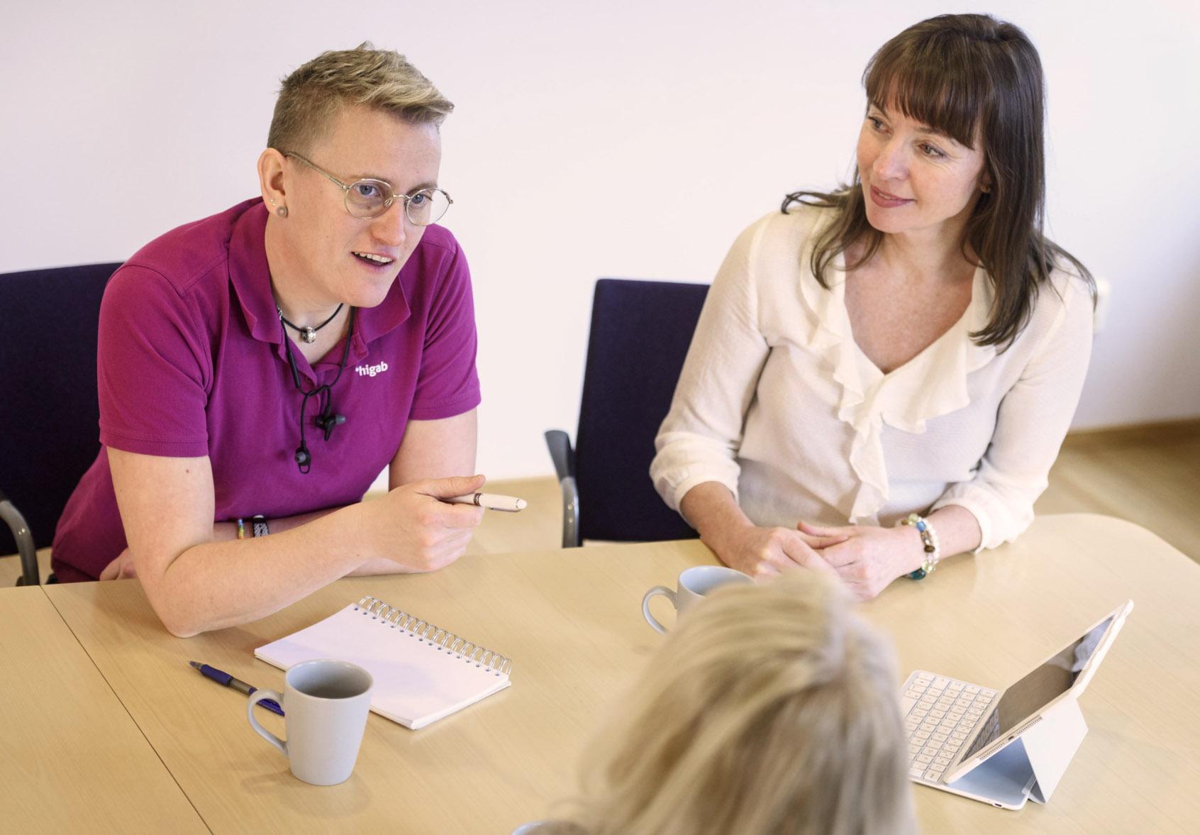 Tre personer pratar i ett möte