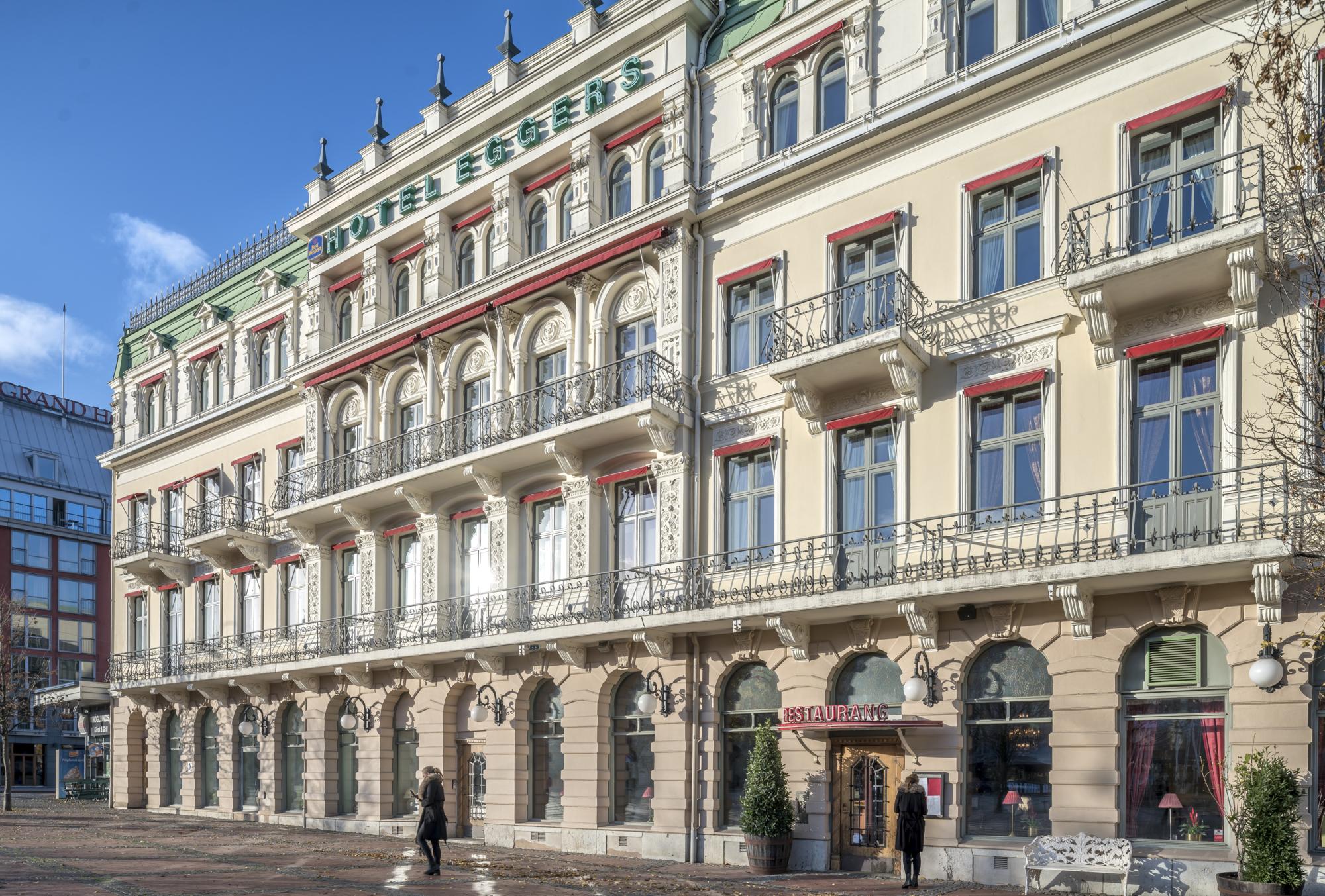 Den vita stenfasaden med balkonger på Hotel Eggers.