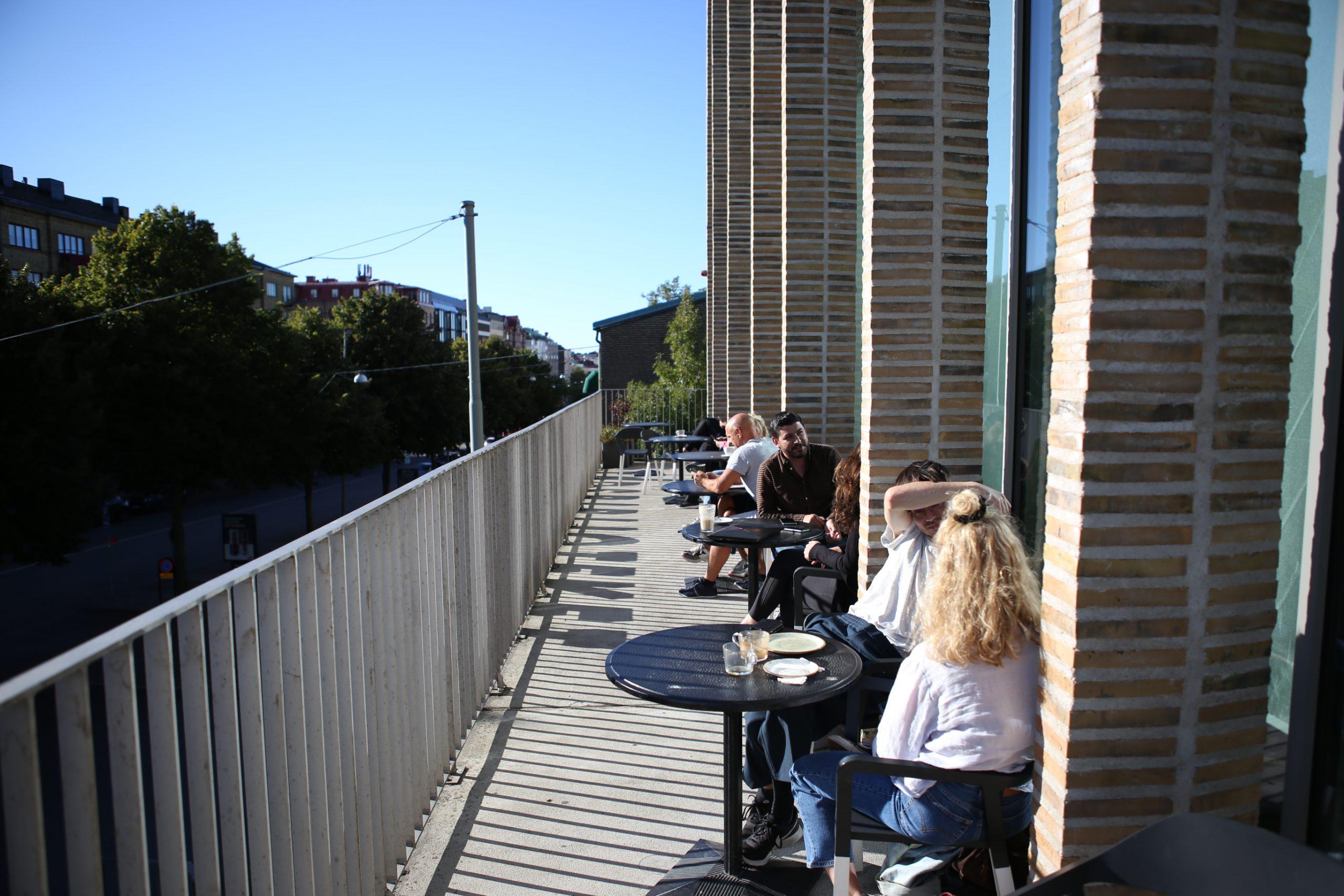 Cafégäster sitter ute i solen på Stadsbiblioteket.
