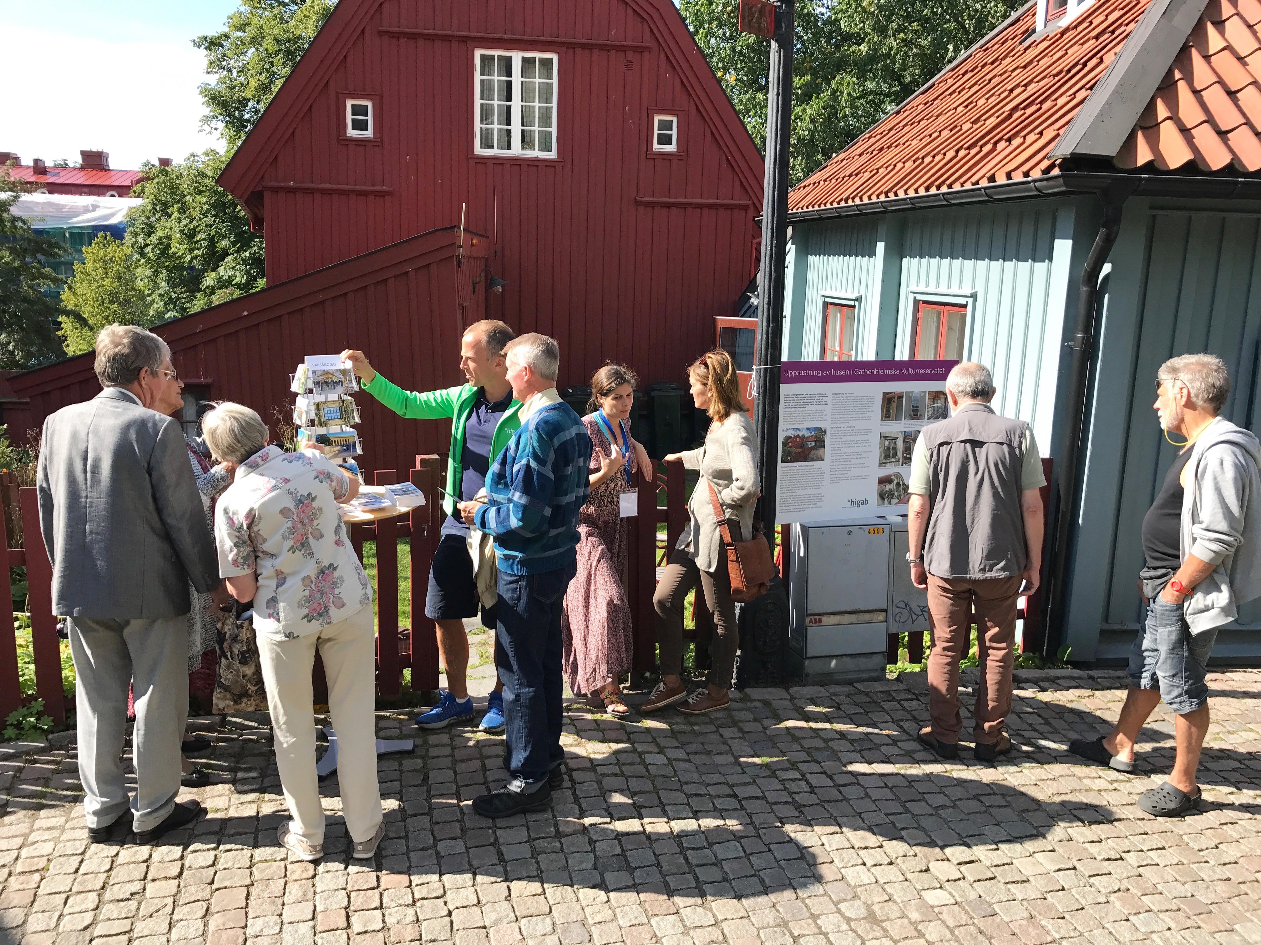 HIgabs personal talar med besökare framför två av husen i Gathenhielmska Kulturreservatet