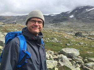 Bild på Tomas Bech med vandringsklädsel i bergen