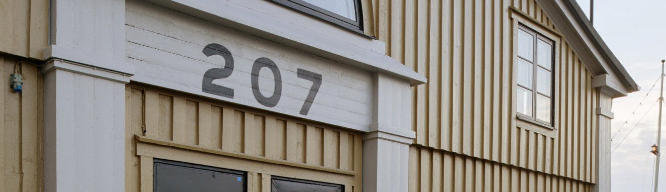 Närbild på träfasaden på Kajskjul 207 med siffran 207 skriven på fasaden.