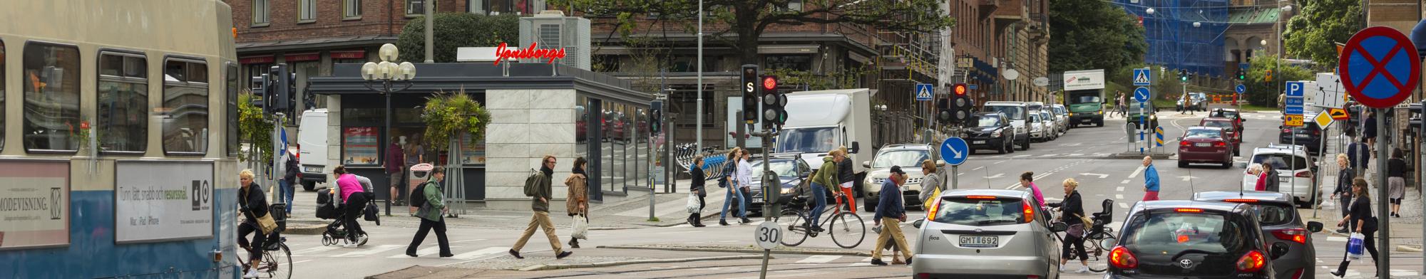 Folk i rörelse på Avenyn framför en kiosk.