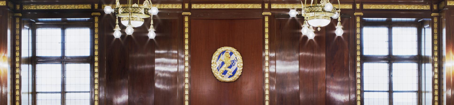 Trävägg, takkronor och Göteborgs-emblem i kommunfullmäktigesalen i Börshuset.