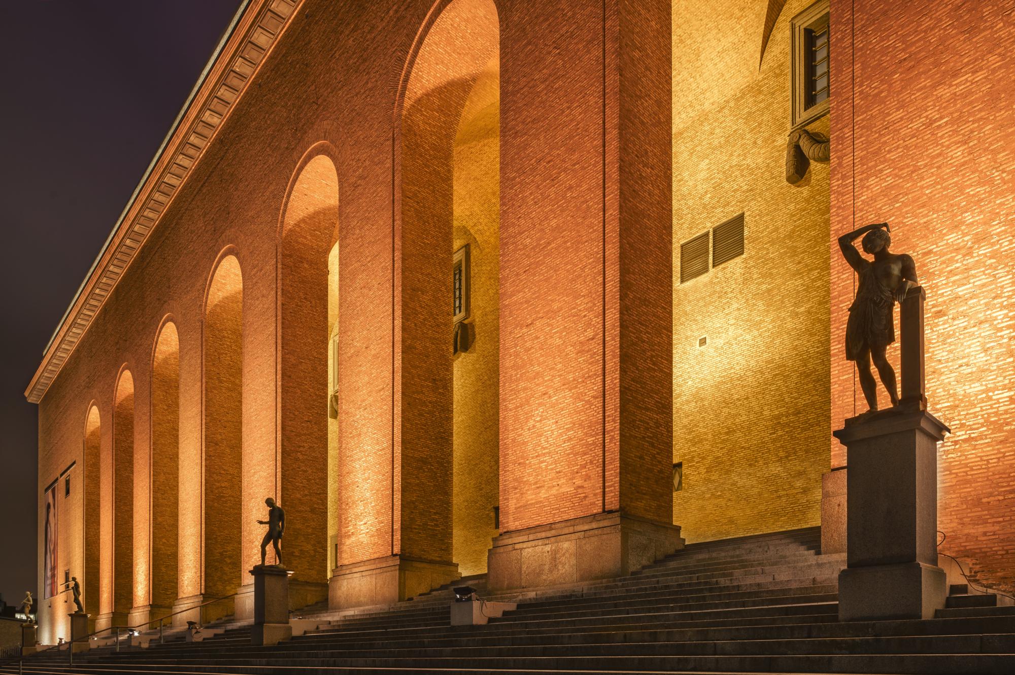 Del av Göteborgs konstmuseums fasad framifrån belyst med orange ljus