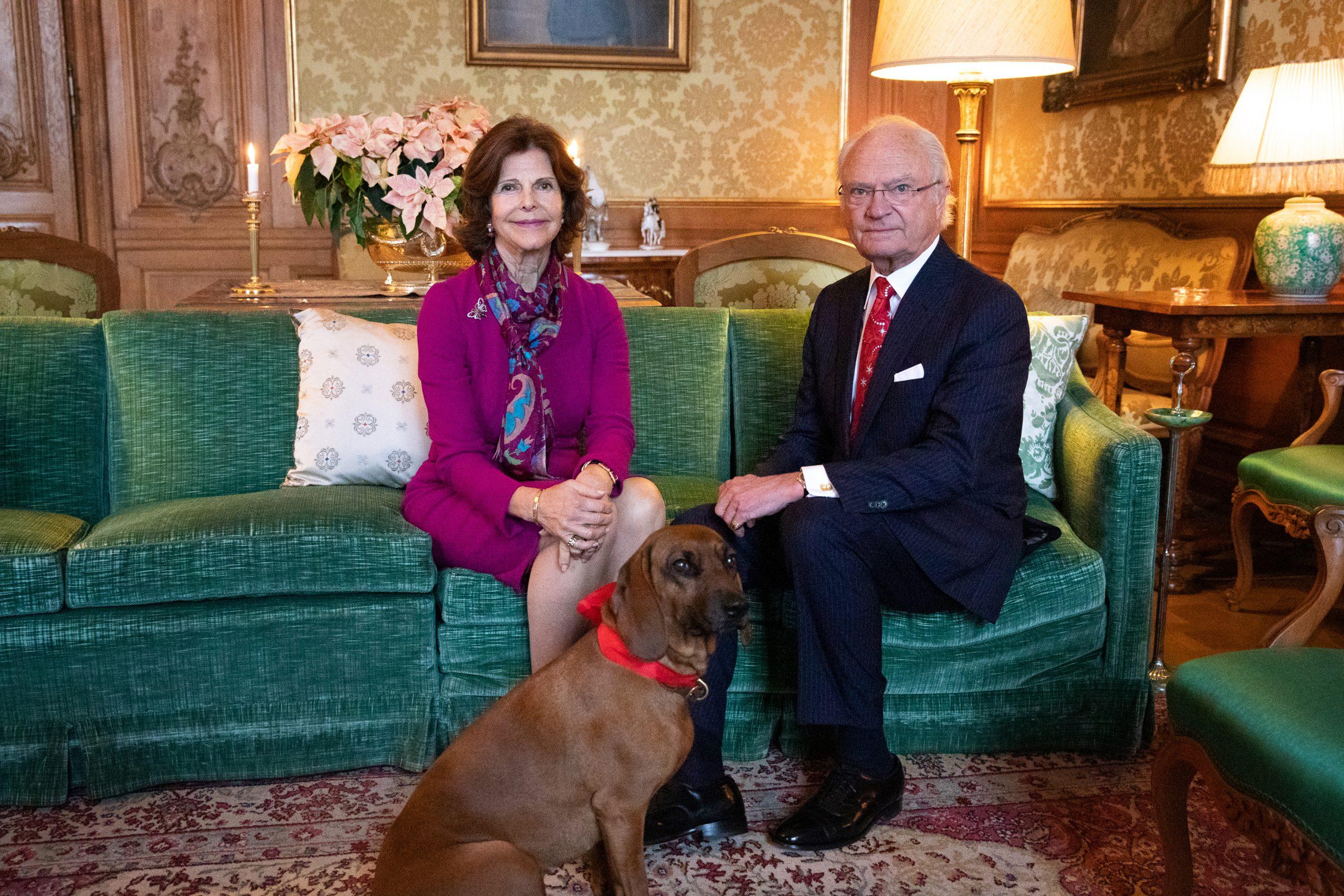 Det svenska kungaparet sitter i en soffa med sin hund.