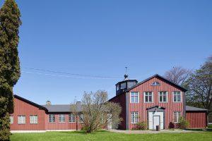 Grönska framför röd träbyggnad i Kviberg.