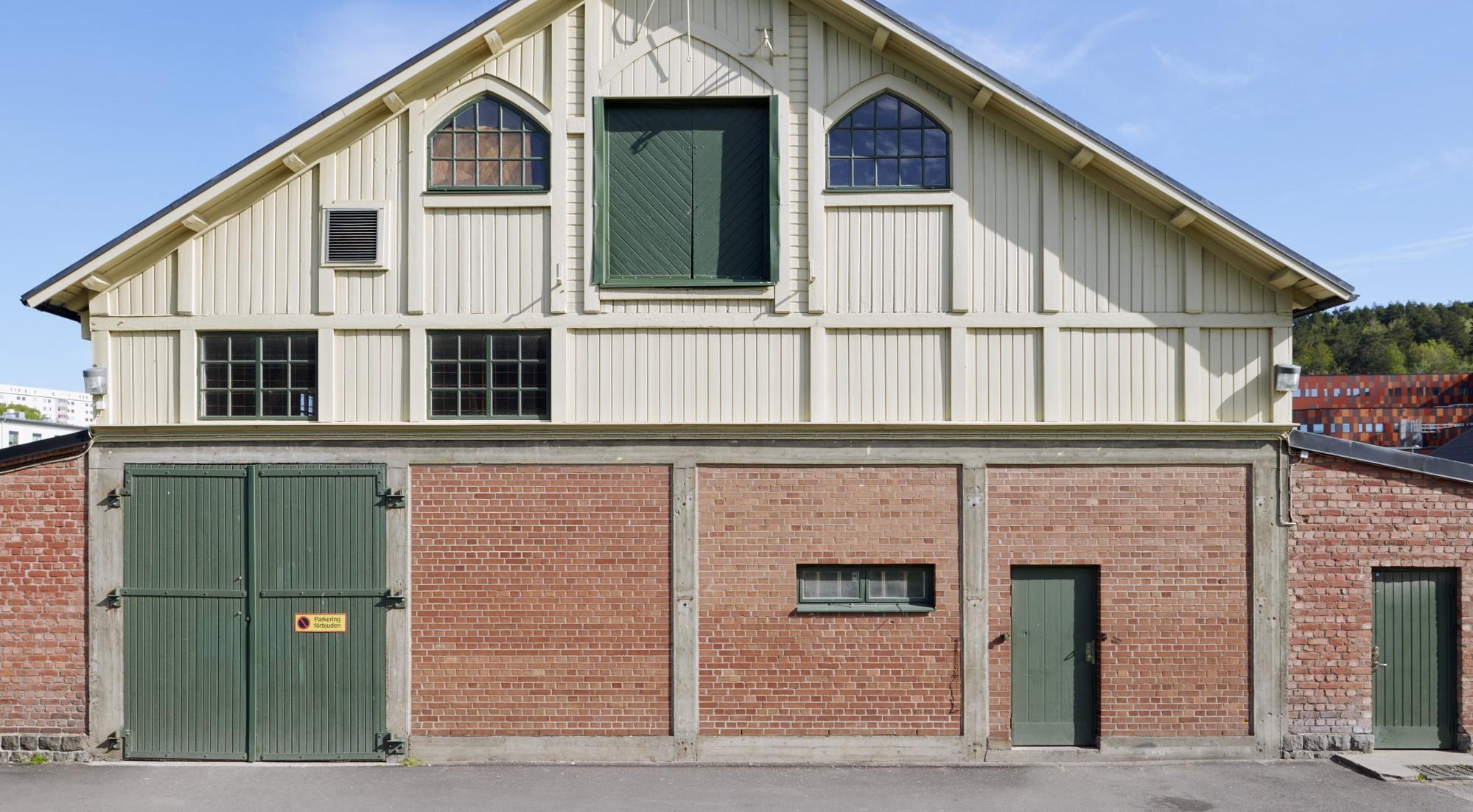 Utsidan av en av stallarna på Kvibergs Kaserner. Nederdelen av fasaden är i rött tegel och överdelen är i gult trä med snedtak.