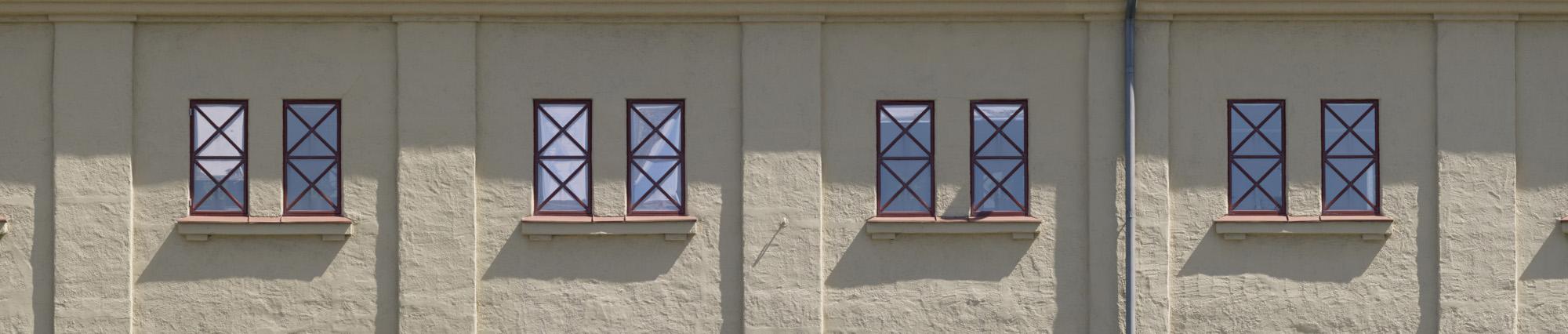 Lagerhusets gula stenfasad med röda fönster.