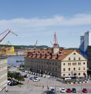 Vy över det gula stenhuset Lagerhuset och Göta Älv med kranar.