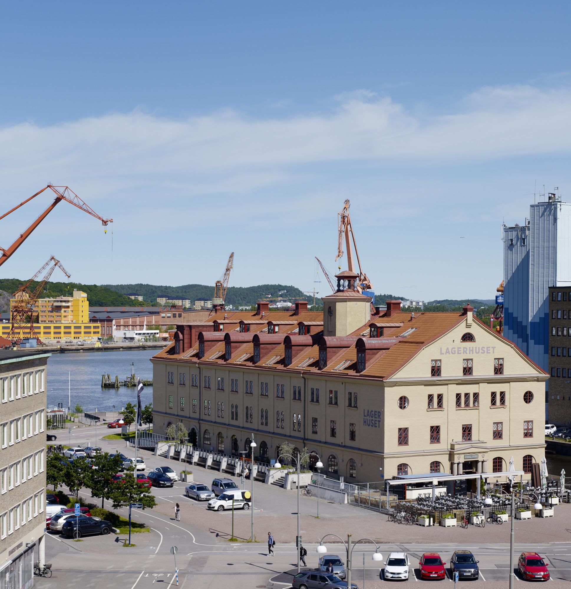 Utsikt mot det gula stenhuset Lagerhuset och Göta Älv med kranar.