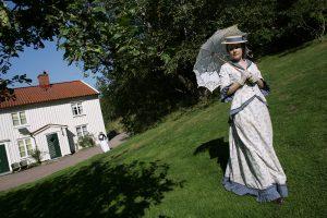 Kvinna står utklädd på gräsmattan framför det vita trähuset Lilla Änggården