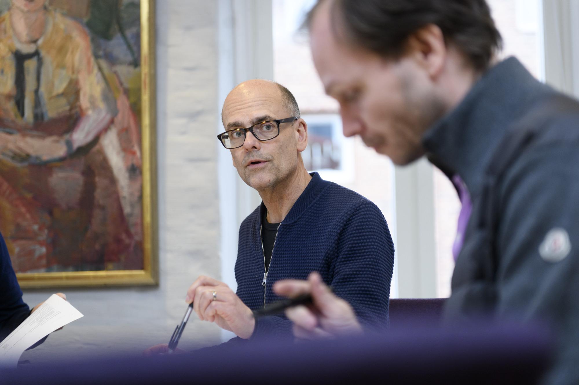 Higab-medarbetaren Svante Thun sitter med en penna i handen och pratar med kollegan Christian Motter.