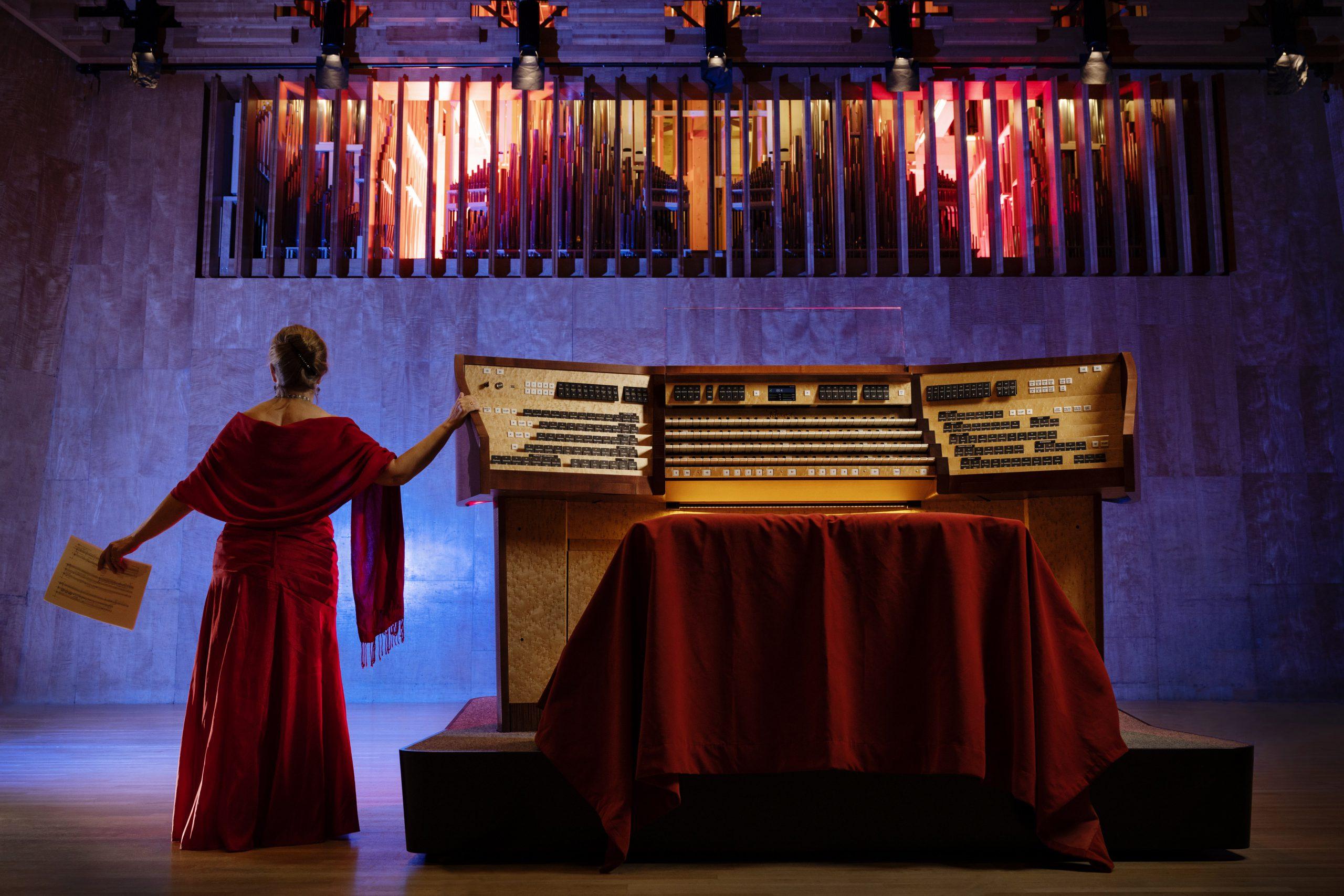 Kvinna står vid orgelbord och orgel.