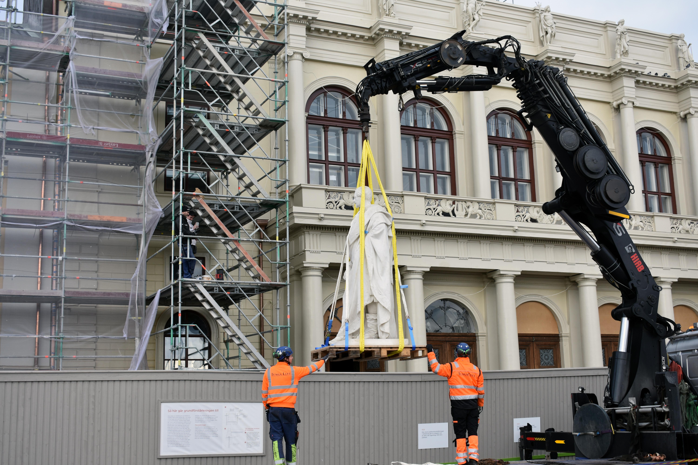 Lyftkran lyfter staty över träplank och dirigeras av två byggnadsarbetare