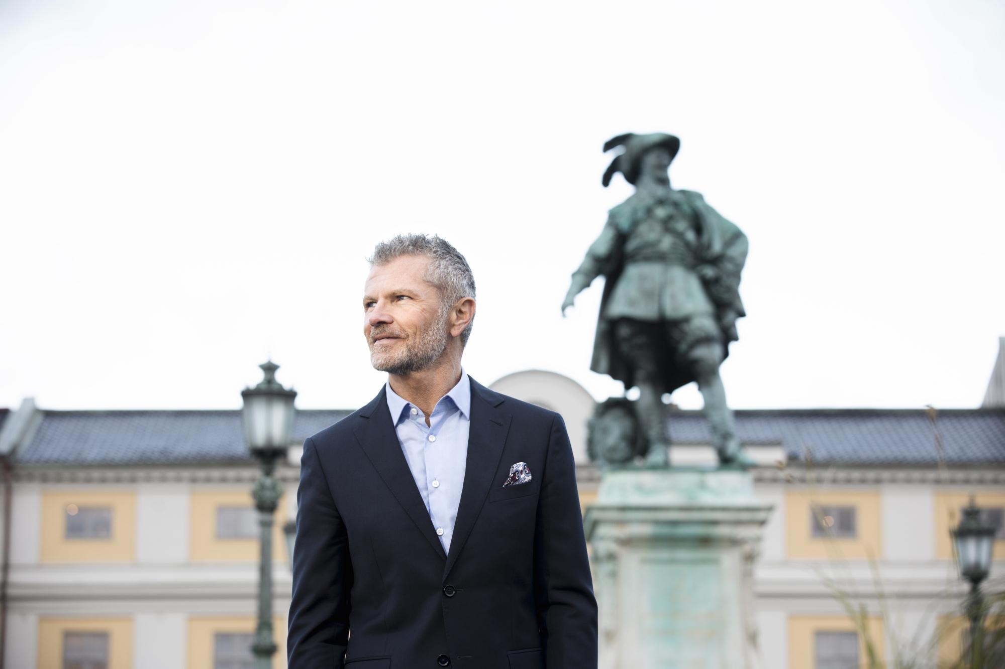 Higabs vd Per-Henrik Hartmann står på Gusta Adolfs Torg framför statyn föreställandes Gustav II Adolf.