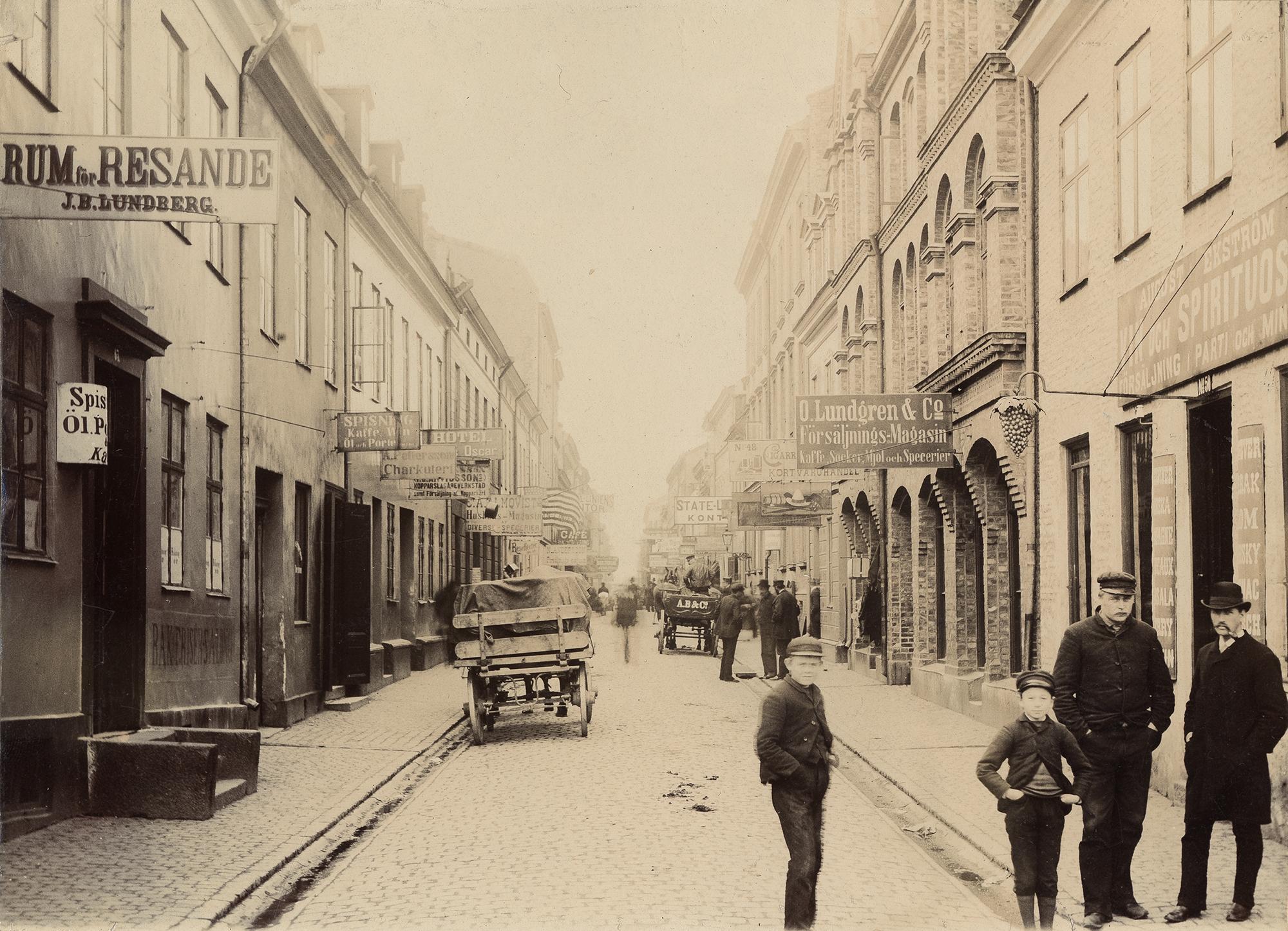 Postgatan, då Sillgatan, fotad 1888. Fyra personer syns i förgrunden och kollar in i kameran.