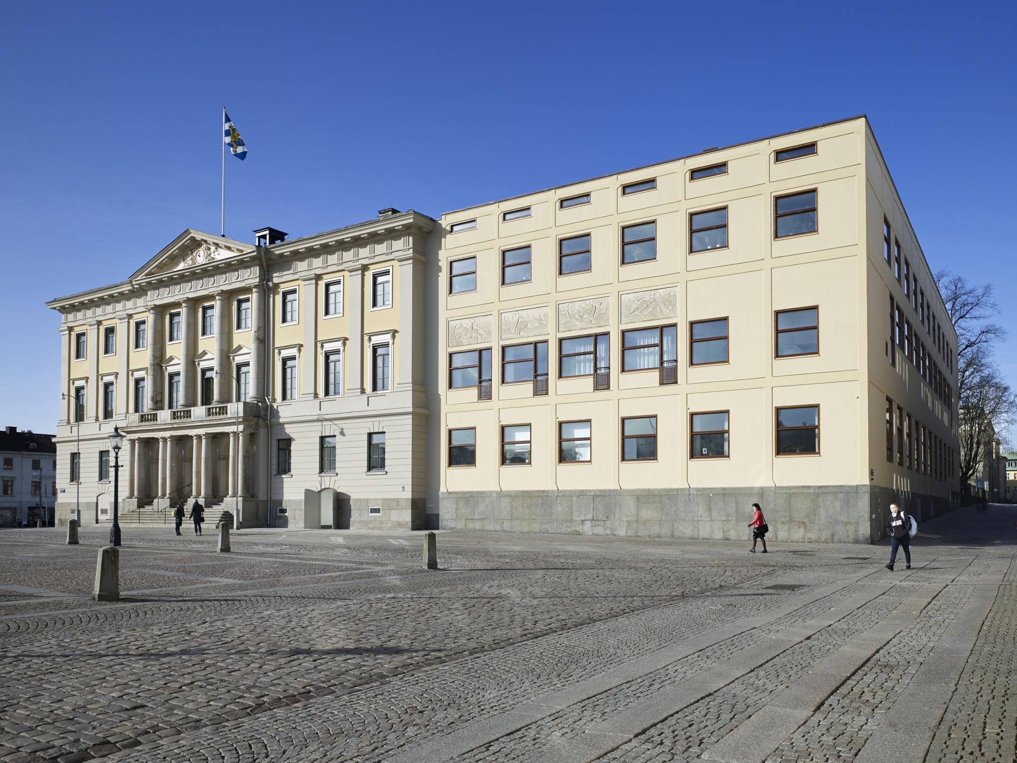 Fyra personer går förbi Rådhuset på Gustaf Adolfs Torg.