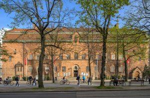 Gående och cyklister passerar Vasagatan utanför den röda tegelbyggnaden Röhsska museet.