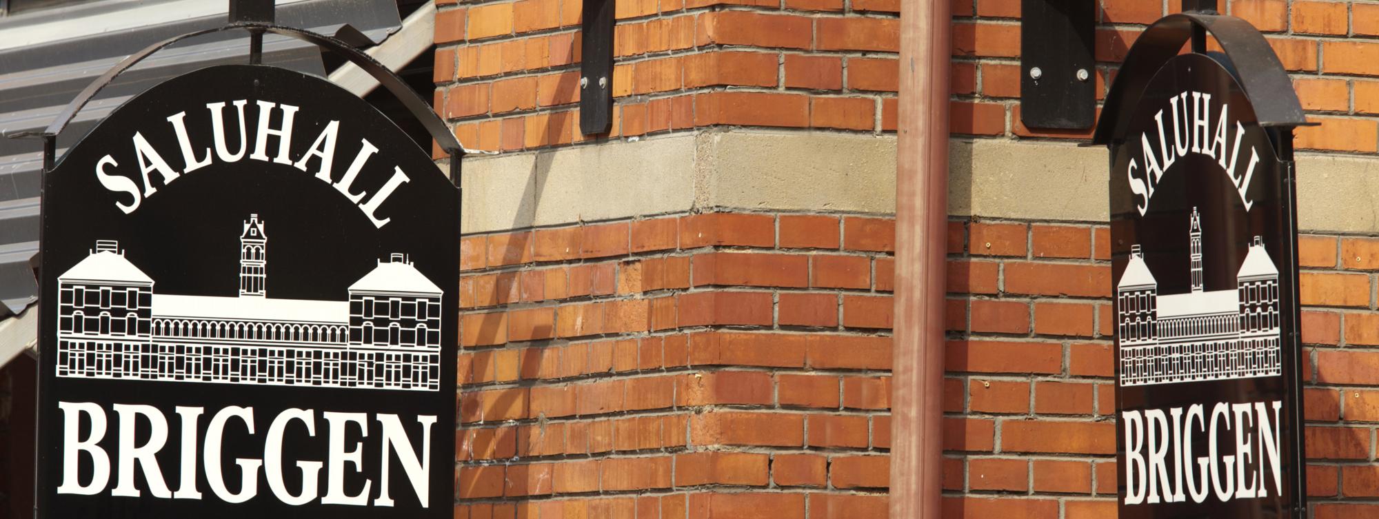 Skyltar hänger på en röd tegelfasad med texten Saluhall Briggen.