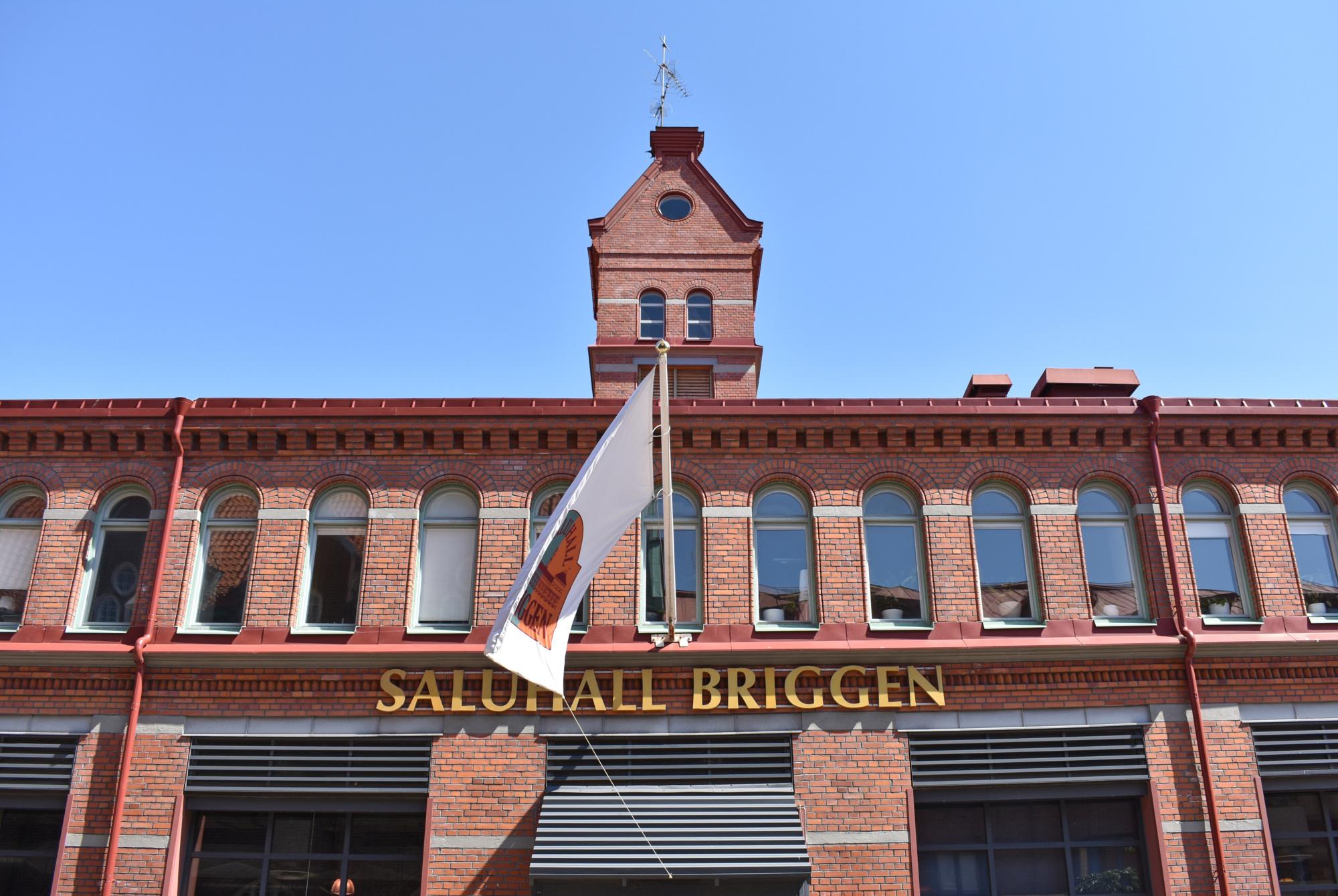 Tegelfasad med flagga och texten Saluhall Briggen