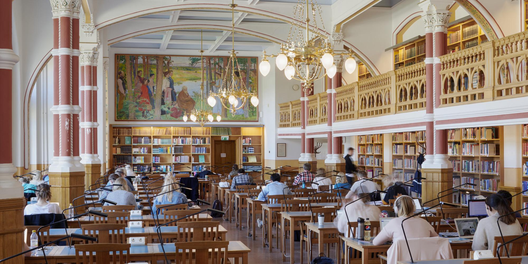 Studenter sitter vid sina bänkar i läsesalen.
