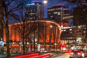 Scandinaviums fasad lyser i orange färg och runt omkring åker bilar.