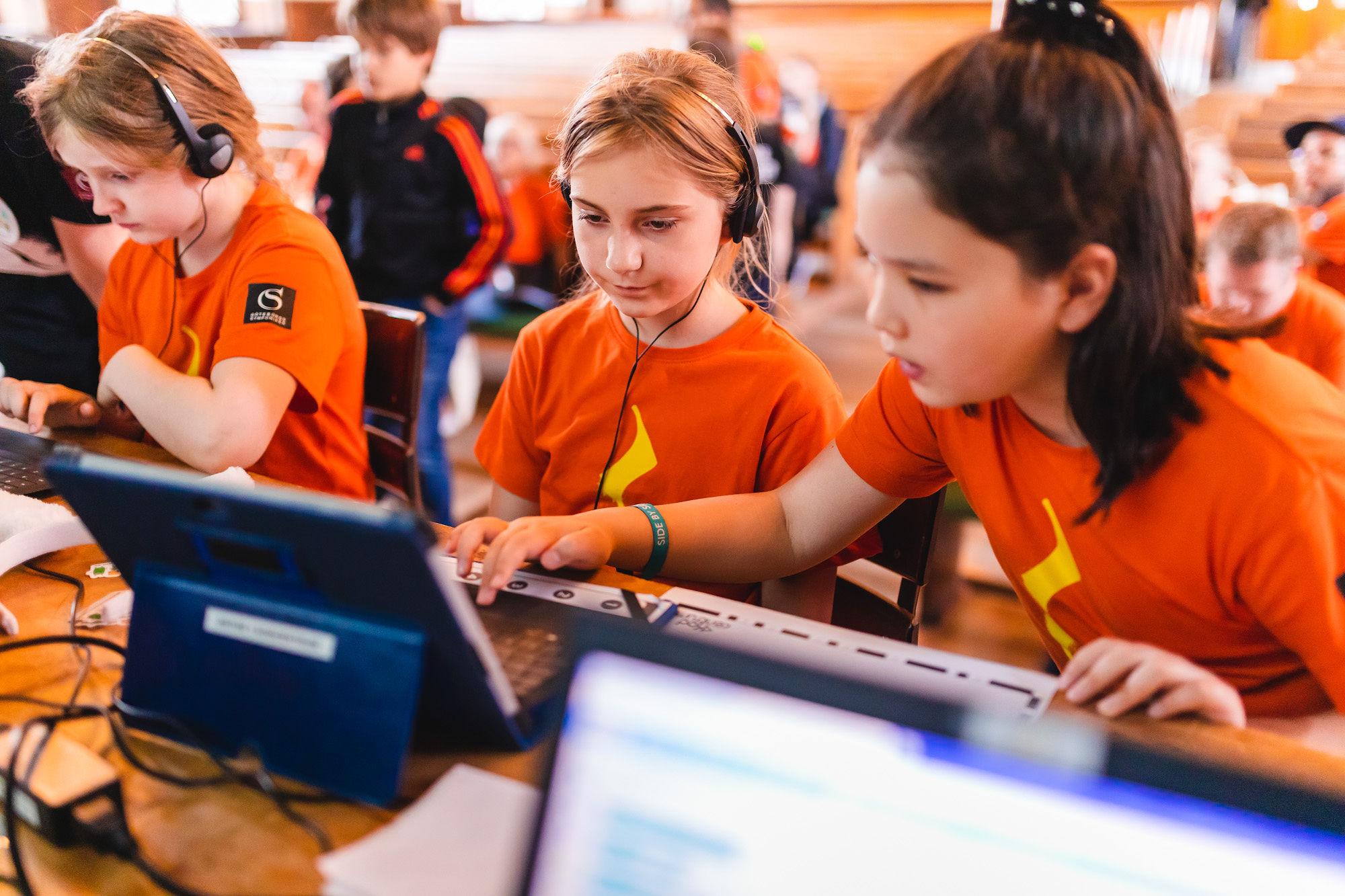 Barn med hörlurar framför datorer