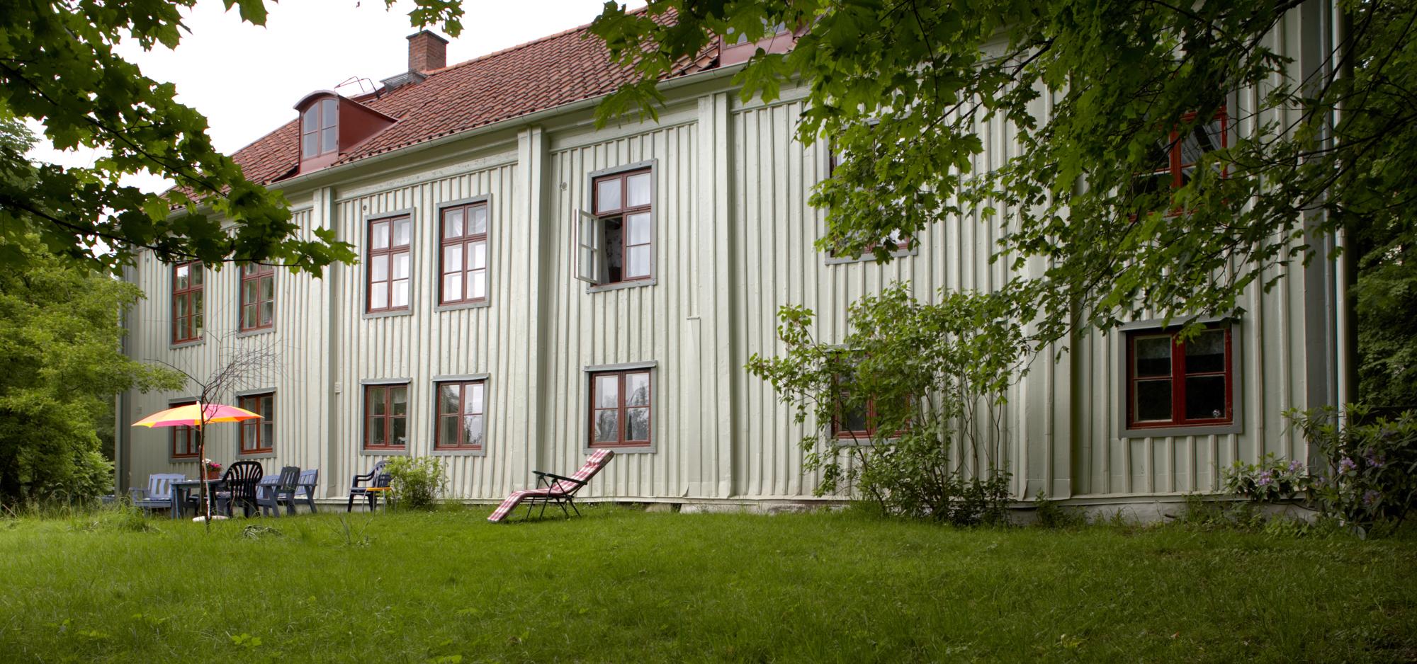 Skårs Gårds grönskande baksida med trädgårdsmöbler.