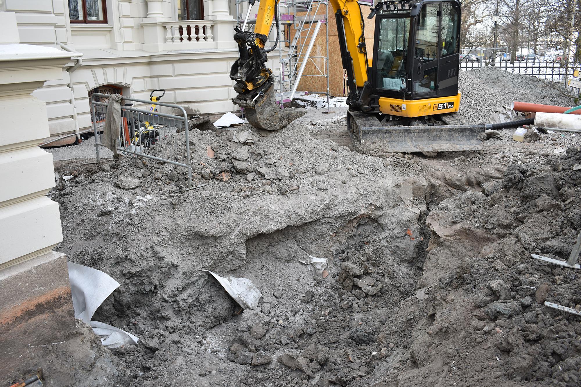 Grävskopa gräver på byggarbetsplats.