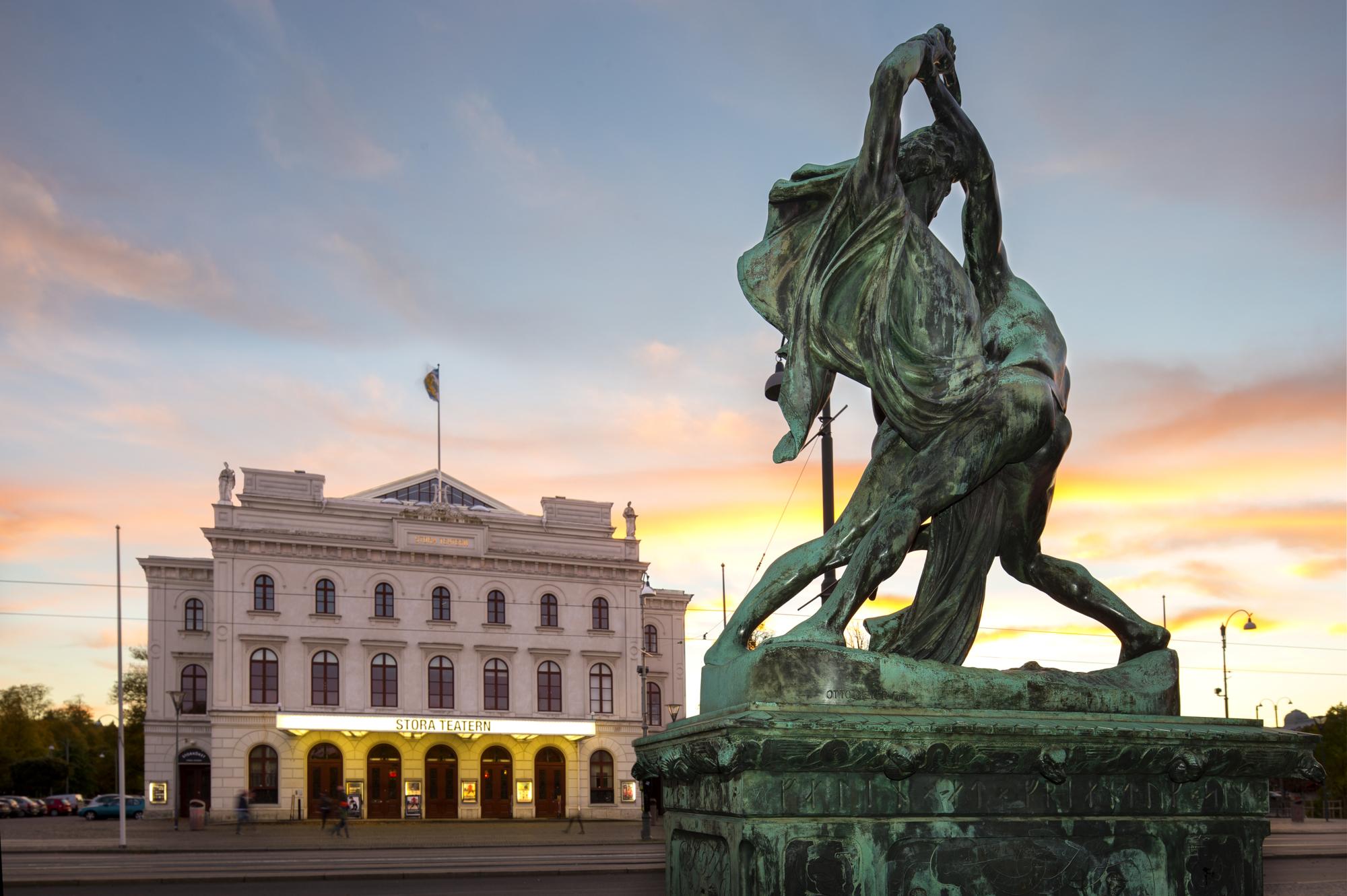 Staty framför ett upplyst Stora Teatern.