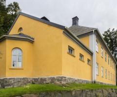 Utsidan av det gula stenhuset Gullbergsbrohemmet.