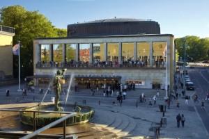 Folk i rörelse på Götaplatsen och framför Poseidon-statyn och Konserthuset