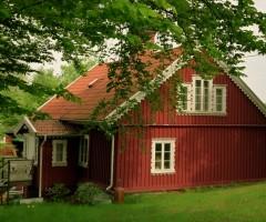 Grönska runt det rödmålade Nilssons Hus.