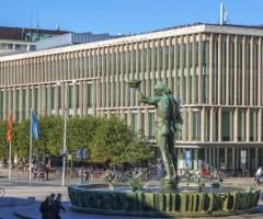 Folk i rörelse runt Poseidon-statyn och Stadsbiblioteket vid Götaplatsen.