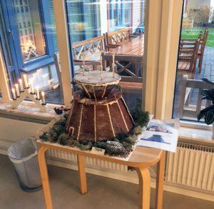 Ett pepparkakshus står på ett bord.